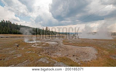 Vapor steam rising off Black Warrior hot springs geyser and Hot Lake in Yellowstone National Parks Lower Geyser Basin in Wyoming United States