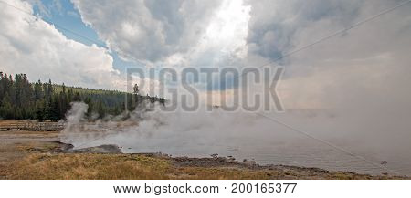 Mist and Steam rising off Black Warrior hot springs geyser and Hot Lake in Yellowstone National Parks Lower Geyser Basin in Wyoming United States