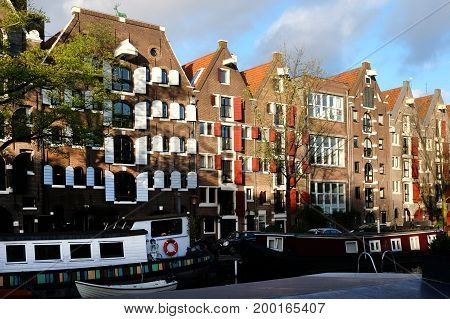 Buildings and boats in the street of Amsterdam in sunny day Netherlands