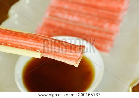 imitation crab stick made from fish dipping with soy sauce on chopsticks
