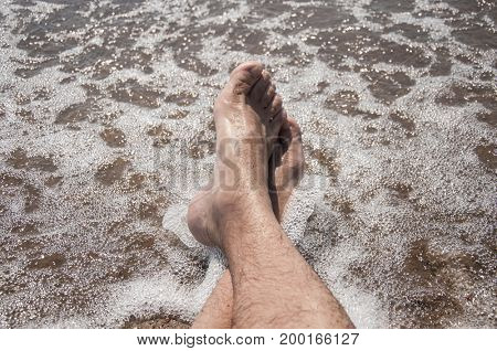 Male feet on a pebble beach and sea waves at sunset