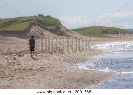 Teenage boy walking alone along an empty beach beautiful sand dunes and glittering waves of the ocean solitude outdoors activity concepts and background with space for text