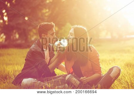 A loving couple of teenagers. Sudden picnic in the park at sunset. Teens drink soft drinks sitting on the lawn.