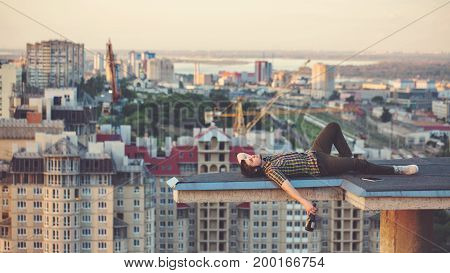 A hipster guy drinks wine from a bottle on the roof of a high-rise building in the city center. He relaxes after a day's work and lies on the roof.