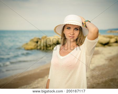 Beautiful middle-aged woman in hat on the beach. The concept of relaxing on the beach.