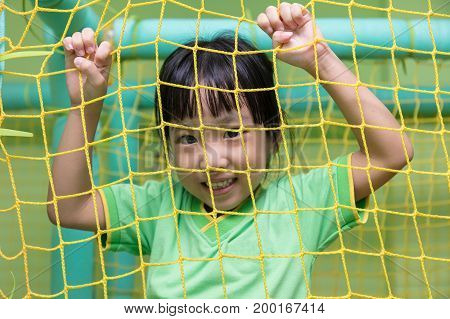 Asian Chinese Little Girl Playing Behind The Net