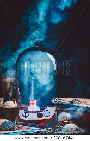 Handcrafted paper boat with steam under glass dome. Still life with captain workplace. Dark background with copy space.