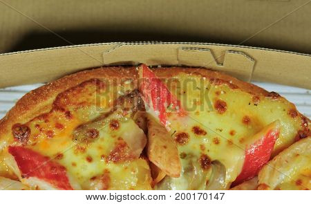 Close up of pizzas with variety of toppings and cheese in cardboard take out boxes with open lid