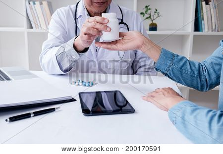 Doctor Giving Pills To Male Patient In Clinic. Concept Of Healthcare, Medical Treatment And Insuranc