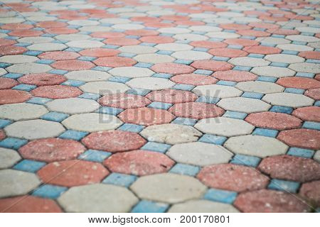 Octagon and square shape cement block pavement in random color pattern selective focus.