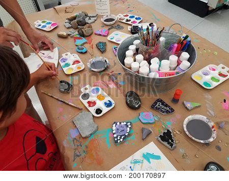 child painting rocks on a table with many colored paints