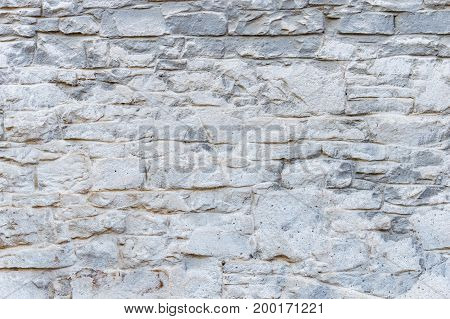 Background texture of an old stone wall hue sharkskin, smeared with white paint.
