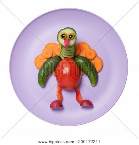 Funny vegetable peacock compiled on pink plate