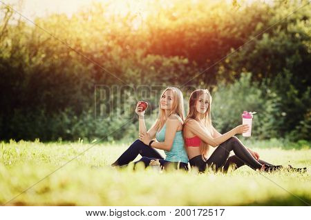Group of two girls sitting on grass holding an apple and bottle of water, doing sports fitness and yoga. Concept healthy food on training, friendship, joy, diet, vitamins.