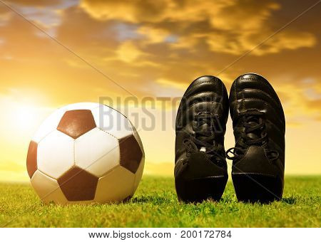 Soccer ball and shoes on football playground at sunset.
