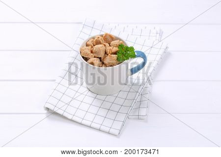 mug of soy meat cubes on checkered dishtowel