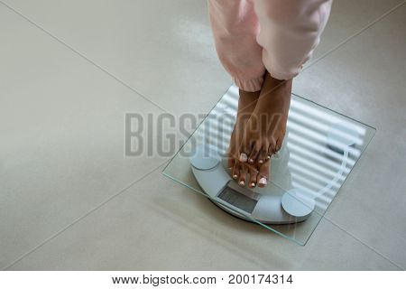 Low section of woman standing on bathroom scale at home