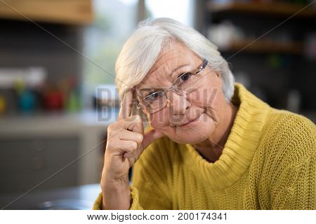 Close-up of worried senior woman in the kitchen