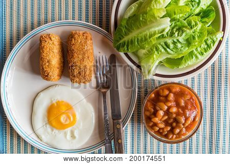 Croquettes fried egg fresh vegetables white kidney beans in tomato sauce as a breakfast
