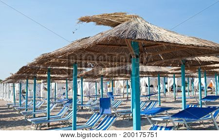 Picture of blue sunbeds and retro umbrellas on the romanian seaside Vama Veche