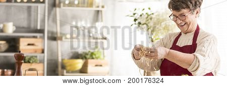 Lovely smiling grandma preparing tasty homemade pasta in cozy kitchen