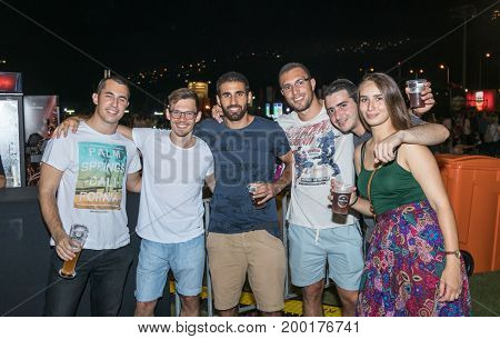 Haifa Israel August 16 2017 : A group of young visitors positively poses near the counter at the traditional annual beer festival in the city of Haifa in Israel
