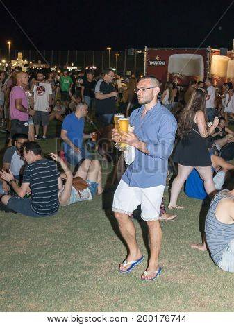 Haifa Israel August 16 2017 : A young man goes and carries two glasses of beer at the traditional annual beer festival in Haifa Israel