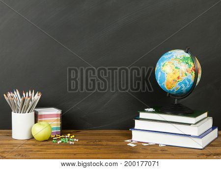 School supplies with globe pencils stack of books and an apple on blackboard background with copyspace for your text design. Back to school concept