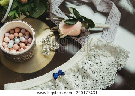decorated wedding bouqet near garter and boutonniere on chair