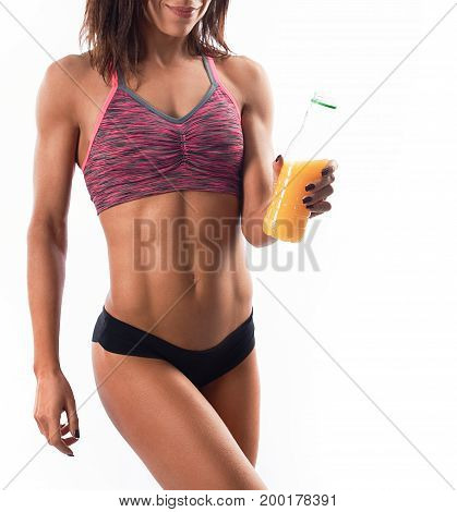Vertical studio portrait of a young sportswoman wearing top and shorts holding a bottle of fresh delicious vitamin juice isolated on white.