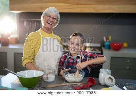 Granddaughter mixing flour in a bowl while posing with grandmother in the kitchen