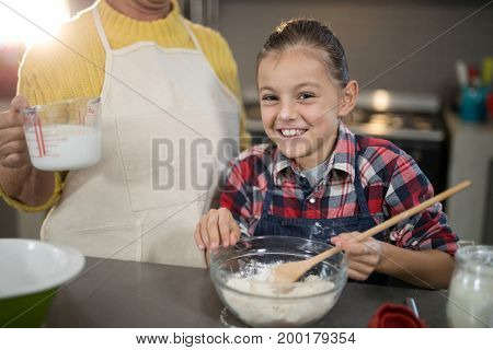 Grandmother adding water while granddaughter is mixing flour in a bowl in kitchen