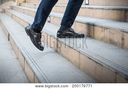 Close up legs of young Asian businessman walking upstairs outside office in the city business concept copy space. Feet of traveling man in leather black shoes