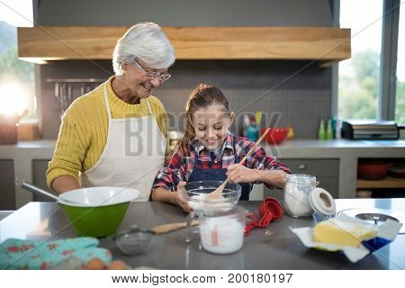 Granddaughter mixing flour in a bowl in the kitchen poster