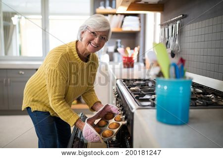 Senior woman taking tray of fresh cookies out of oven in kitchen at home