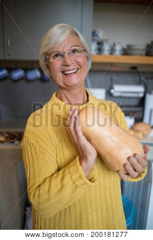 Portrait of smiling senior woman holding squash in kitchen at home