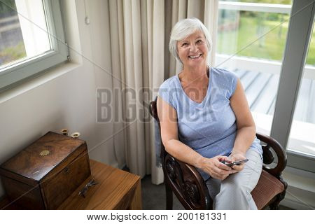 Portrait of smiling senior woman sitting on chair with mobile phone in living room