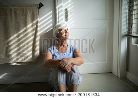 Tense senior woman looking through window in bedroom
