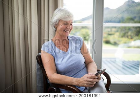 Smiling senior woman using mobile phone on chair in living room