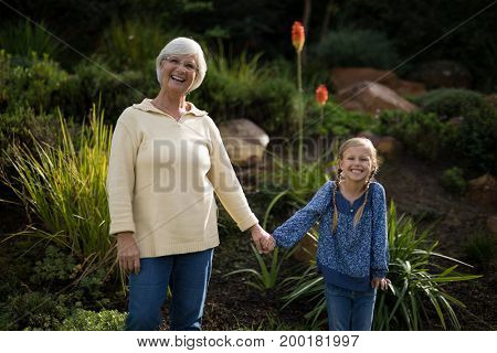 Portrait of smiling granddaughter and grandmother standing in garden on a sunny day