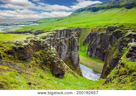 The striking canyon in Iceland. The concept of active northern tourism. Bizarre shape of cliffs surround the stream with glacial water. Green Tundra in July