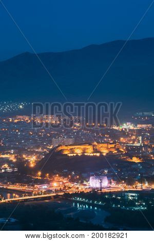Gori, Shida Kartli Region, Georgia. Gori Fortress In Cityscape In Evening Illumination Under Blue Sky. Travel Destination In Night Lights. Goris Tsikhe Is A Medieval Citadel