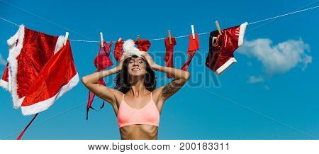 christmas girl with happy face wear santa hat near red coat sock bra shorts and garter sunny summer outdoor on blue sky background