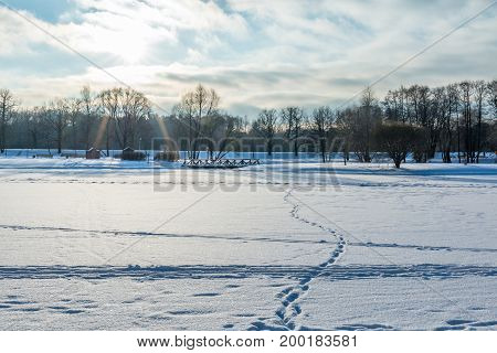 Winter landscape with a frozen lake footprints in the snow a wooden bridge and the sunset sky over the trees.