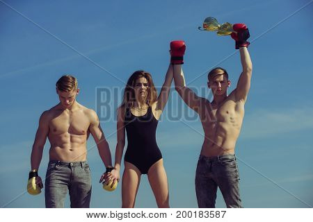 Boxer workout and healthy fitness. Men and coach outdoor on blue sky. Sport people or team work. Winner and loser in boxing gloves with girl. Woman and twins with muscular body hold champion cup.