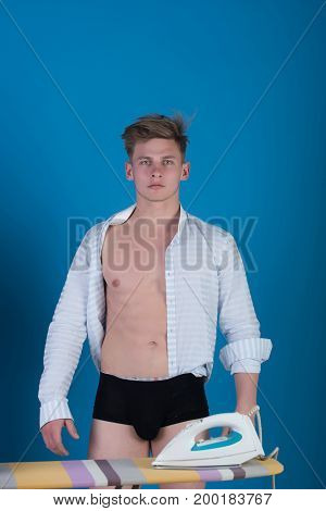Man with muscular torso in open shirt and black underpants standing at ironing board with iron on blue background. Housework and fashion concept