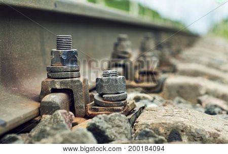 Low angle view of the screws fixing railroad rail close up