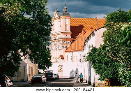 Grodno, Belarus. People Walking Near Catholic Church Of The Annunciation Of The Blessed Virgin Mary And A Bridgettine Monastery At Sunny Summer Day In Hrodna, Belarus