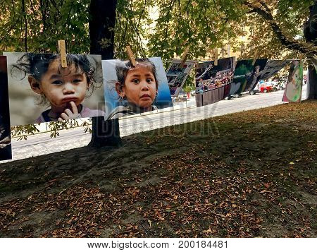 LVIV UKRAINE - AUGUST 13: Photos of sad faces of children hanging on clothespins during the charity exhibition
