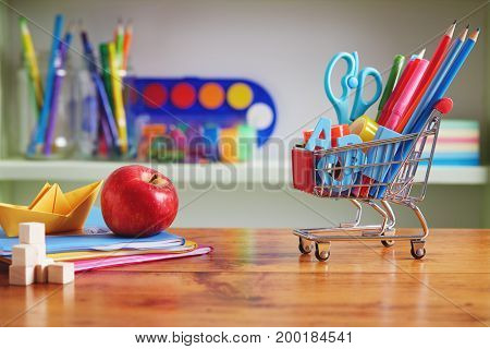 Back to School Shopping Cart with Supplies on Wooden Table. Shopping cart filled with with school necessities.